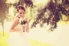 Bride outdoors smelling her wedding bouquet Royalty Free Stock Photo