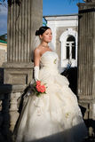 Bride in the park. Attractive young bride with bouquet in the park. Brunette near column looks up stock photography