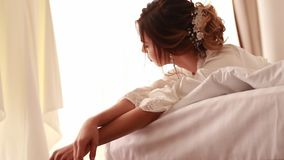 The bride in peignoir lies on bed. The bride in white peignoir lies on the bed on the day of her wedding stock video