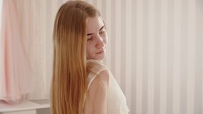 The bride in a peignoir strokes her hair and smiles stock footage
