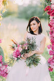 Bride with the peonies bouquet is sitting in the wedding flower arch at the background of the spring forest. Close-up. Portrait Stock Photo