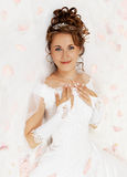 Bride in petals of roses. Beautiful young bride on the white background with petals of roses Royalty Free Stock Photography