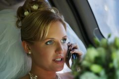 The bride with the phone. In the automobile royalty free stock photo