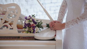 Bride at the Piano. Wedding flowers lie on the keys of the piano stock footage