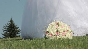 The bride picks up the wedding bouquet of roses lying on the grass. Bride in white dress and shoes in hand takes the bouquet stock video footage