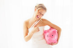 Bride with piggy bank showing thumbs up Royalty Free Stock Images