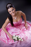 Bride in pink. Happy young bride posing in a pink wedding dress, holding bouqet of white flowers Stock Photo