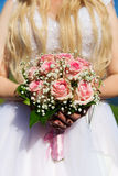 Bride with pink roses bouquet in her hands Stock Image