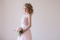 Bride in a pink wedding dress and bouquet of flowers Royalty Free Stock Image