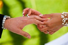 A bride places a ring on the grooms hand stock photography