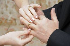 Bride placing ring on finger Stock Image