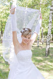 A bride playfully puts up her veil Stock Photography