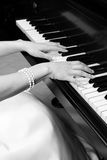 Bride playing piano. Bride with pearl bracelet playing piano royalty free stock image