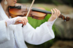 Bride playing on violin for groom in summer park Stock Image