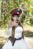 Bride in a police cap and a gun Stock Image