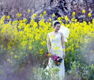 Bride portraint with white wedding dress in cole flower field Royalty Free Stock Images