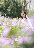 Bride portraint with white wedding dress in Orychophragmus violaceus flower field. A Chinese Bride with white wedding dress in Orychophragmus violaceus flower Royalty Free Stock Photos