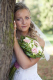 Bride portrait. Portrait of an young bride with flower bouquet peeking from behind of a tree Royalty Free Stock Photos
