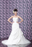 Bride portrait. Young adult bride in white wedding dress posing over magenta wall. Her hair decorated with lily flowers Stock Photos