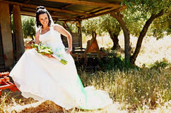 Bride portrait. Beautiful bride portrait with bouquet. In background we see an old garage with agriculture machinery Royalty Free Stock Photo