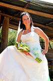 Bride portrait. Beautiful bride portrait with bouquet. In background we see an old garage with agriculture machinery Stock Photography