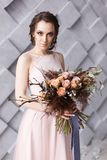 Bride portrait. Young beautifull woman holding bouquet on geometric gray background in studio. Looking straight royalty free stock image