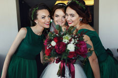 Bride poses with bridesmaids reaching out her hand with bouquet Stock Photo
