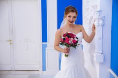 The bride poses in a hall with blue walls and white gypsum pillars. She is surprised at the beauty of the interior and. Touches the statue. The girl smiles not Stock Images
