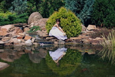 Bride poses on a pond Royalty Free Stock Photography