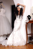 Bride posing. Brunette bride with long and curly hair posing in bridal shop royalty free stock image
