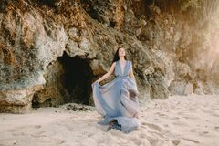 Bride posing in blue wedding dress in beach at sunset or sunrise colors. Bride posing in blue wedding dress in beach at sunset or sunrise. Wedding style Stock Photos