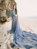 Bride in wedding dress in beach at sunset or sunrise colors. Wedding style. Bride posing in blue wedding dress in beach at sunset or sunrise. Wedding style Royalty Free Stock Images