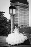 Bride posing next to street lamp bw Stock Image