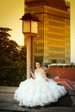 Bride posing next to street lamp Royalty Free Stock Image