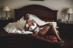 Bride is posing  in whiteness on the background  bed and dress Royalty Free Stock Photos