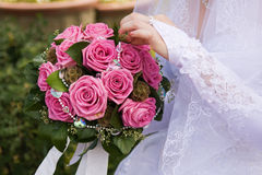 Bride posy. A bride in the white dress holding a posy of pink roses Stock Image