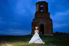 Bride prays near an old ruined church Royalty Free Stock Photo