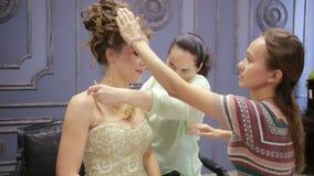 Bride preparing to wedding ceremony, help her make-up artist and hairdresser stock video footage