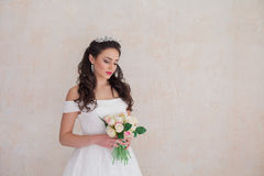 Bride Princess stands in a wedding dress with flowers. Bride Princess stands in a wedding dress with a bouquet of flowers Royalty Free Stock Photo