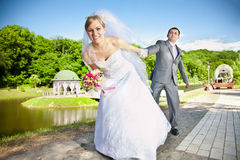 Bride pulling handsome groom by hand at the park Stock Images
