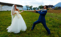 Bride pulling her groom to her with a rope - funny wedding concept. Stock Photos
