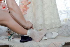 The bride pulls the legs white socks. Royalty Free Stock Images