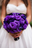 Bride with Purple Bouquet. Close up of a bride holding a purple bouquet Royalty Free Stock Image