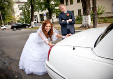 Bride pushing car while groom looking at her Royalty Free Stock Photography