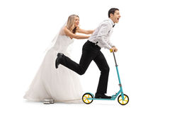 Bride pushing a groom on a scooter Royalty Free Stock Images