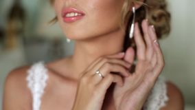 Bride put on earring. Indoors stock footage