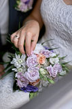 Bride put her hand on the wedding bouquet.  stock image