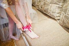 Bride put on pink garter Stock Photos