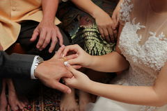 Bride put the wedding ring on groom`s finger. Concept of marriage. Royalty Free Stock Photos