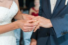 Bride put on the wedding ring on grooms finger royalty free stock photos